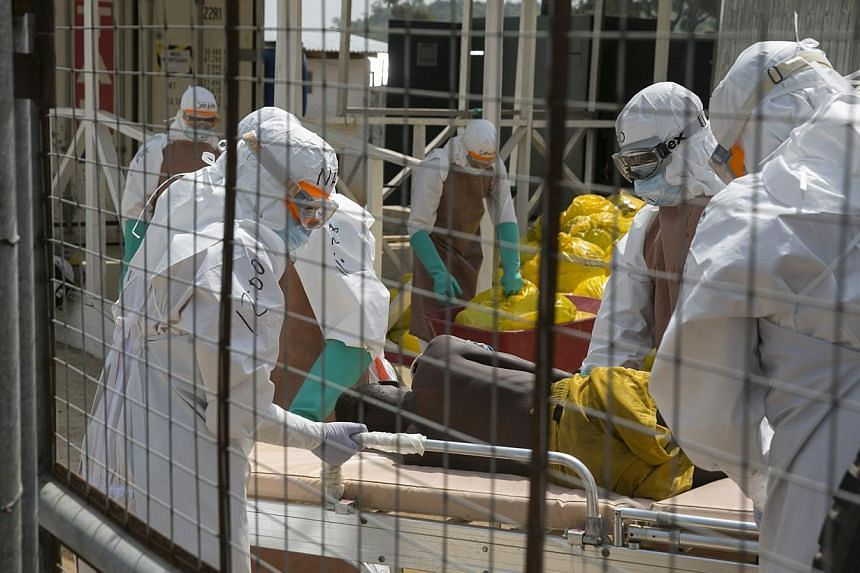 British health workers lifting a newly admitted Ebola patient onto a wheeled stretcher in to the Kerry town Ebola treatment centre outside Freetown, Sierra Leone, on Dec 22, 2014. -- PHOTO: REUTERS