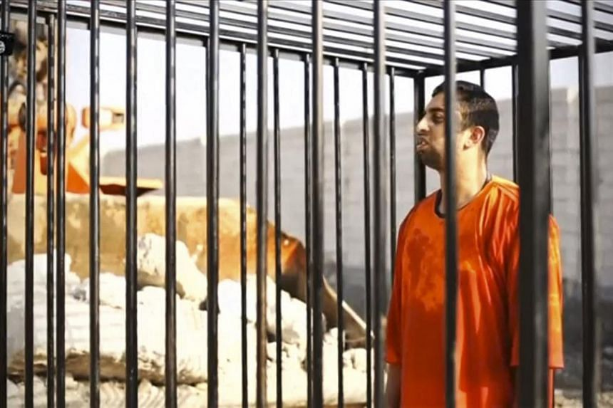 Islamic State captive Jordanian pilot Muath al-Kasaesbeh is seen standing in a cage in this still image from an undated video filmed from an undisclosed location made available on social media on Feb 3, 2015. -- PHOTO: REUTERS