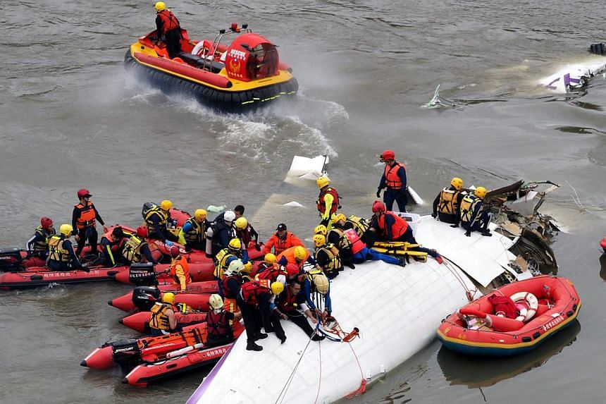 Search and rescue team members operate on a TransAsia Airways passenger plane that crashed into the Keelung River in Taipei, Taiwan, on Feb 4, 2015, shortly after taking-off from the Taipei Songshan Airport for Kinmen Island. Of the 58 people on boar