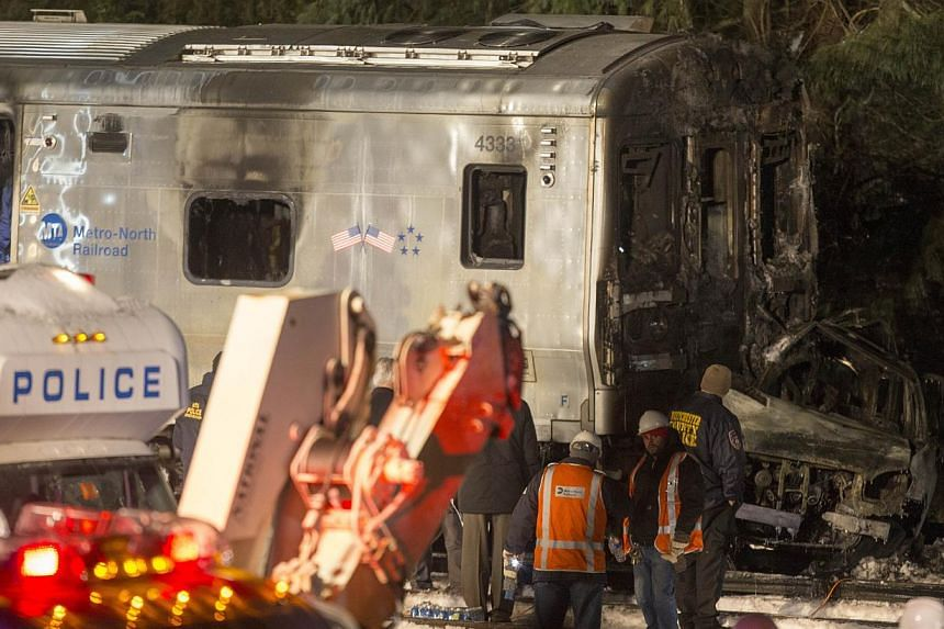 Metropolitan Transportation Authority (MTA) workers and police investigate a Metro-North train crash in Valhalla, New York on Feb 3, 2015. Six people were killed and a dozen injured when a crowded New York commuter train struck a car stalled on the t