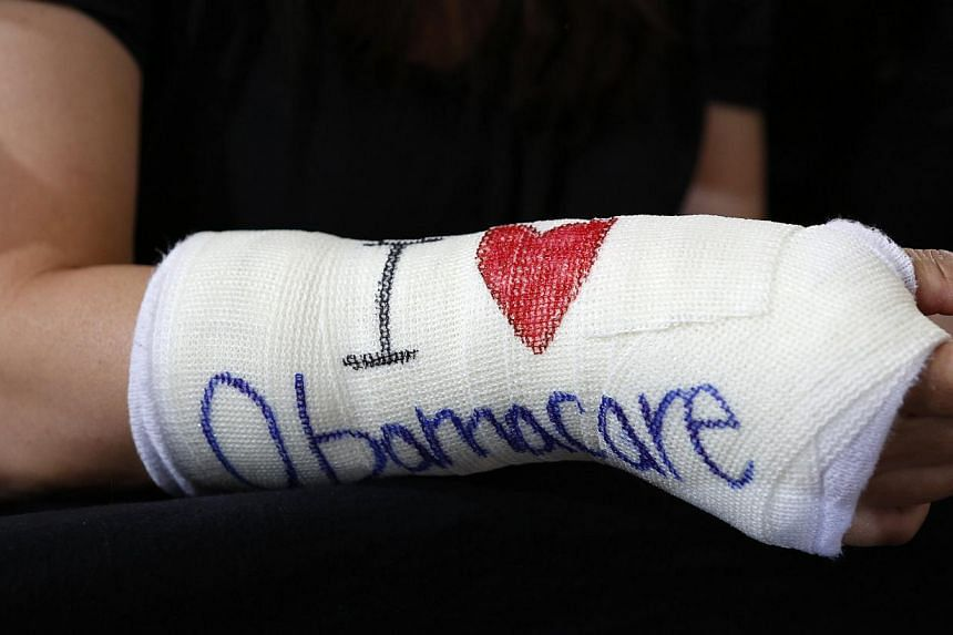 """Cathey Park of Cambridge, Massachusetts wearing a cast for her broken wrist with """"I Love Obamacare"""" written on it, in this Oct 30, 2013 file photo. -- PHOTO: REUTERS"""