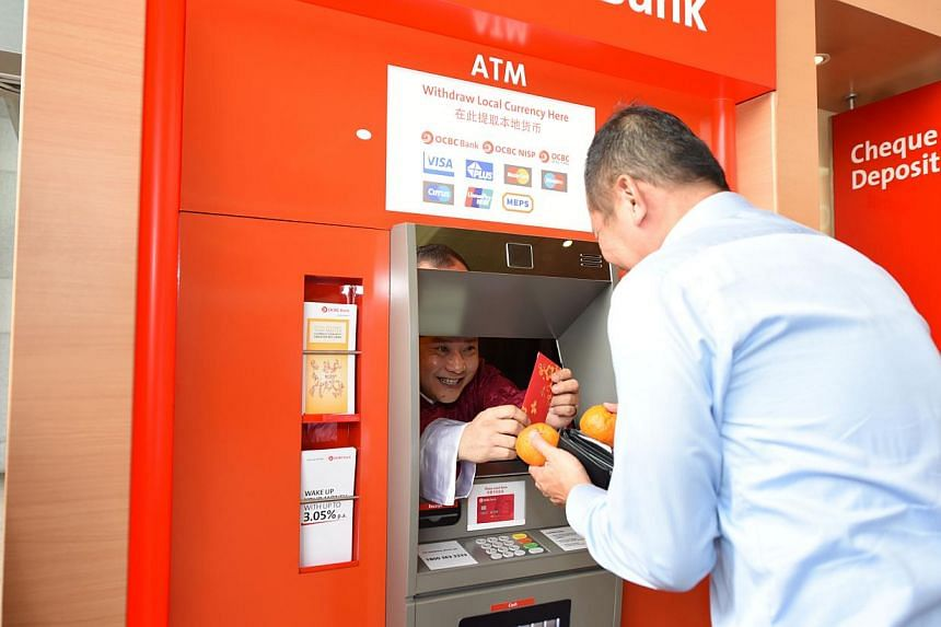 Customers who used their ATM cards at this 'special' ATM machine got a surprise as OCBC's cluster manager Clement Tee popped out from behind the screen dressed up as the God of Fortune, and presented them with a $88 red packet and a pair of manda
