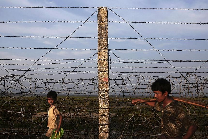"""A Rohingya boy and a man walk along the fence separating Myanmar and Bangladesh on Nov 11, 2014.Myanmar on Wednesday, Feb 4, 2015, condemned a United Nations official for using the term """"Rohingya"""" to describe a persecuted minority that the gove"""