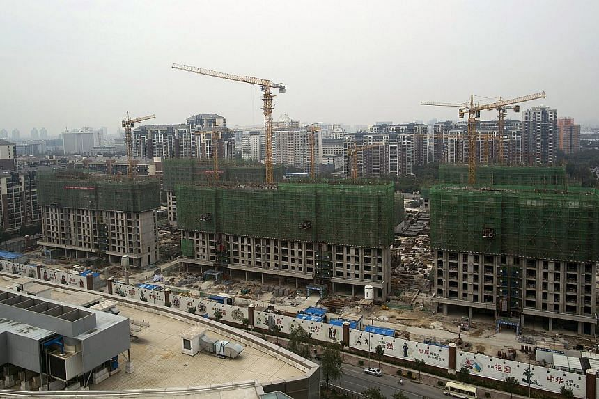 Cranes operating at a residential construction site in the Qinghe district of Beijing, China, on Friday, Sept 12, 2014. -- PHOTO: BLOOMBERG