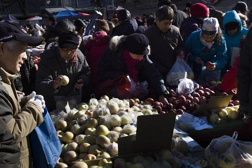 Local residents picking vegetables at a market in Beijing on Dec 5, 2014. -- PHOTO: AFP