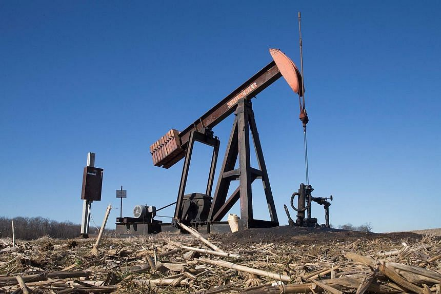 A pump jack, used to extract crude oil from the ground, sits above a well in a farmer's field near Ridgway, Illinois on Jan 21, 2015. -- PHOTO: AFP