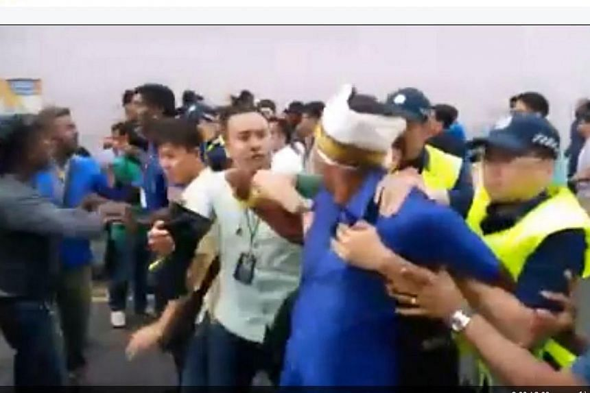 A man is led away by police during the scuffle in a still from a video posted on the Facebook page of Mickey Vikieboy. Three Singaporean men have been arrested for a scuffle with police officers along Desker Road during a Thaipusam procession on