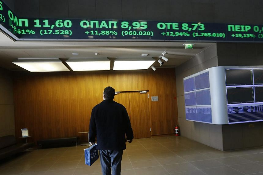 A man looking at monitors inside the Athens stock exchange on Feb 3, 2015. The euro remained higher after jumping 1.2 per cent on Tuesday as Greece's government was said to retreat from a demand for a debt writedown, boosting optimism the region won'