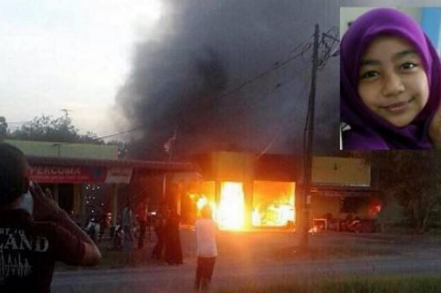 The sundry shop in Jalan Sungai Tiang, Pendang, on fire. Schoolgirl Wan Putri Nur Aisyah Abdullah was inside buying snacks and burnt to death. -- PHOTO: THE STAR/ASIA NEWS NETWORK