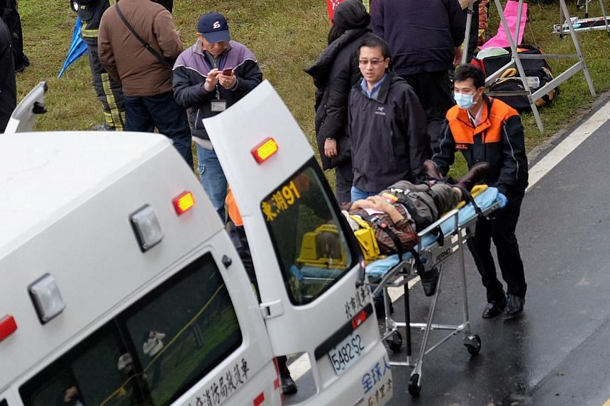 Rescue personnel putting an injured passenger from a TransAsia ATR 72-600 turboprop plane that crash-landed into a river outside Taiwan's capital Taipei into an ambulance in New Taipei City on Feb 4, 2015. The passenger plane with 58 people on board