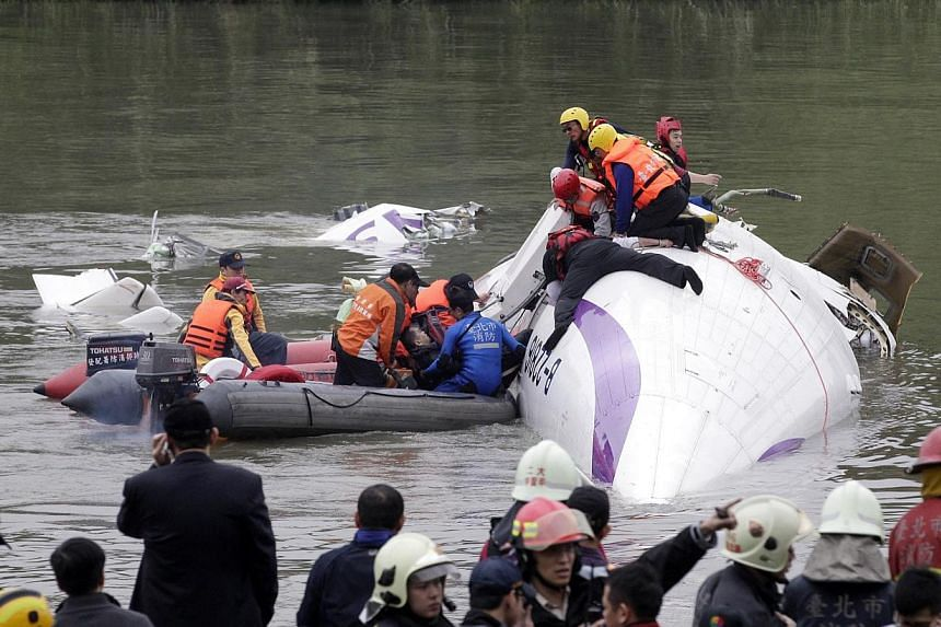 Rescuers pulling a passenger out of the TransAsia Airways plane that crashed in a river in New Taipei City on Feb 4, 2015. -- PHOTO: REUTERS