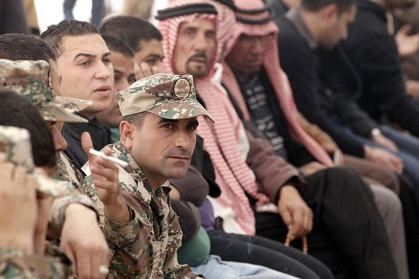 Senior Jordanian army officers and family members gather during a mourning ceremony for Jordanian pilot Maaz al-Kassasbeh at the headquarters of the family's clan in the Jordanian city of Karak on Feb 4, 2015. -- PHOTO: AFP