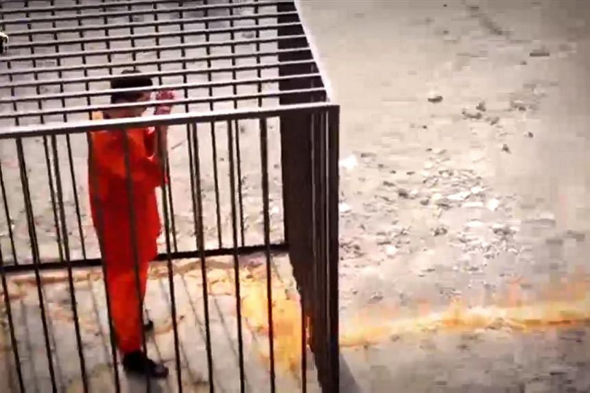 Jordanian pilot Muath al-Kasaesbeh is seen standing in a cage as the flame begins to engulf the metal cage. -- SCREENGRAB / YOUTUBE