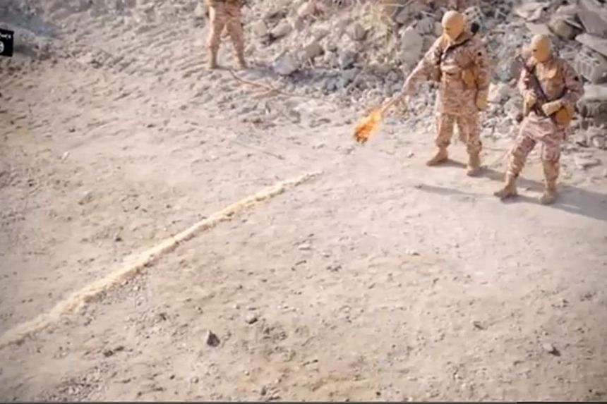 A masked militant uses a torch to light a trail of flame that runs to the metal cage housing Jordanian pilot Maaz al-Kassasbeh. -- SCREENGRAB / YOUTUBE