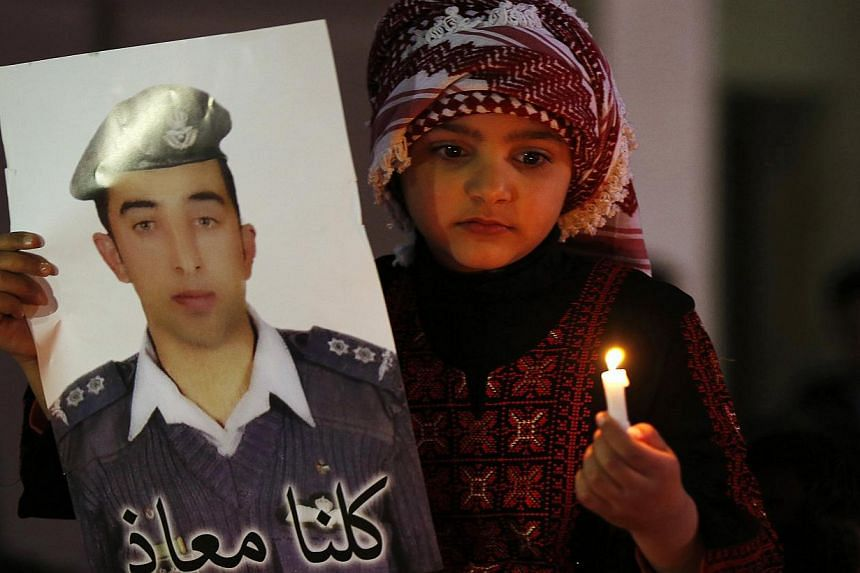 A Jordanian girl holds a poster of pilot Maaz al-Kassasbeh, who is being held captive by Islamic State militants, during a candlelit vigil in Amman Feb 2, 2015. -- PHOTO: REUTERS