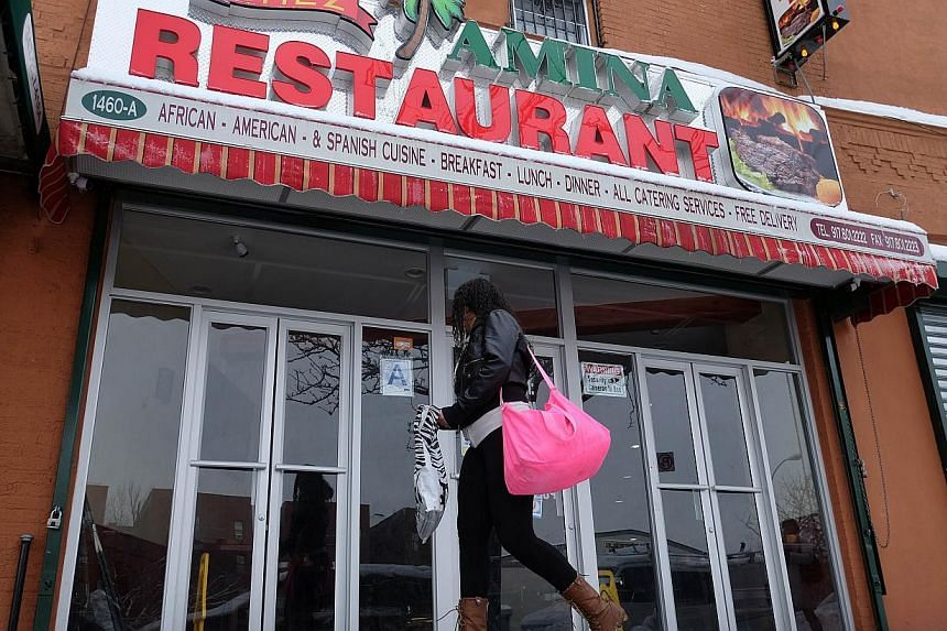 A woman walks past the Chez Amina restaurant in New York's borough of Bronx on Feb 3, 2015. -- PHOTO: AFP