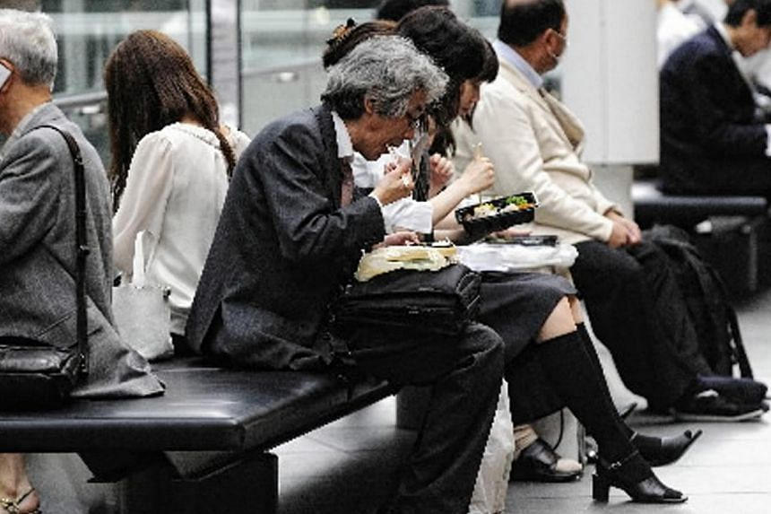 Office workers eat bento lunchboxes in Tokyo, Japan. The country is considering making it compulsory for workers to take at least five days' paid holiday a year, in a bid to lessen the toll on mental and physical health in a country famed for its lon