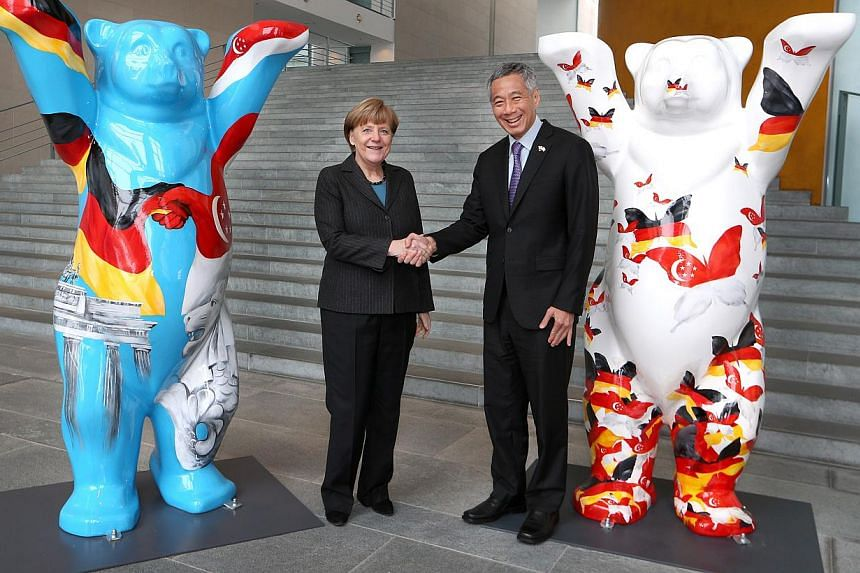 German Federal Chancellor Angela Merkel and Prime Minister Lee Hsien Loong shake hands at the Federal Chancellery in Berlin on Feb 3 2015. They are flanked by the two winning entries of the Buddy Bear Design competition organised by the Singapore Emb