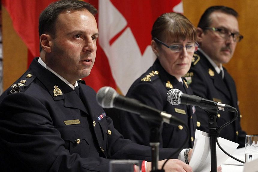 From left to right, Assistant Commissioner James Malizia, of the Royal Canadian Mounted Police (RCMP); Chief Superintendent Jennifer Strachan, RCMP Criminal Operations Office, and Deputy Commissioner Scott Tod listen to reporters' questions at RCMP h