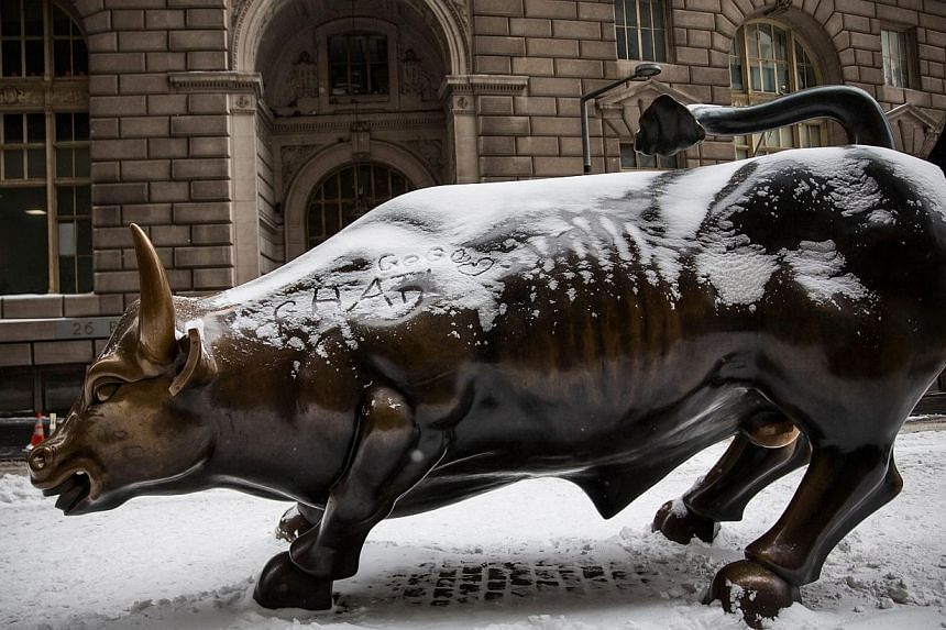 The Wall Street Bull, officially called Charging Bull, is covered in snow after recent snowstorms in New York City. -- PHOTO: AFP
