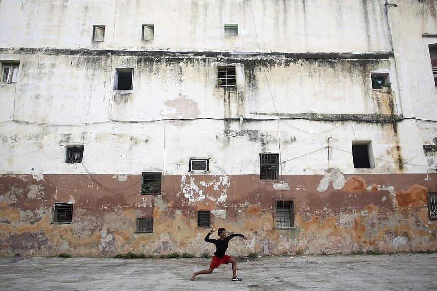 Student Ivan Ramos, 15, plays baseball in downtown Havana on Christmas day last year. -- PHOTO: REUTERS