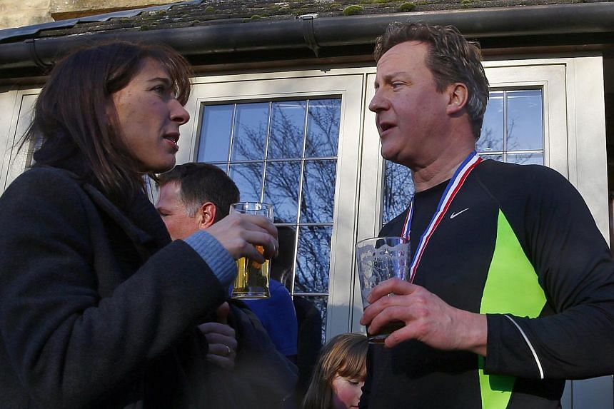 British Prime Minister David Cameron enjoys a beer with his wife Samantha (left) after competing in the Great Brook Run, a mile-long course through water and mud, at Chadlington in southern England Dec 29, 2014. -- PHOTO: REUTERS
