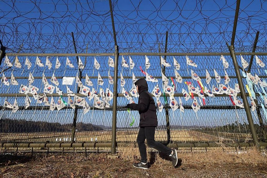A South Korean tourist walking along a barbed wire fence at the Imjingak peace park at the border city of Paju near the Demilitarized Zone dividing the two Koreas on Jan 1, 2015. An army sergeant has been sentenced to death by a military court for ki
