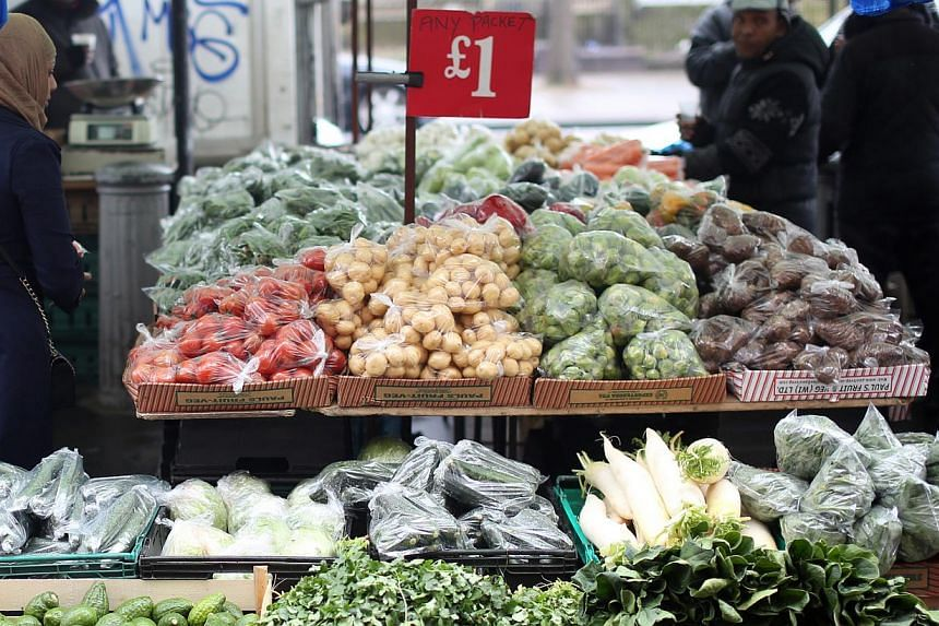 A vegetable stall at an outdoor market in London on March 25, 2014. Food prices in British supermarkets took their biggest fall in more than eight years last month, due to tough competition and falling prices for many raw materials. -- PHOTO: BLOOMBE