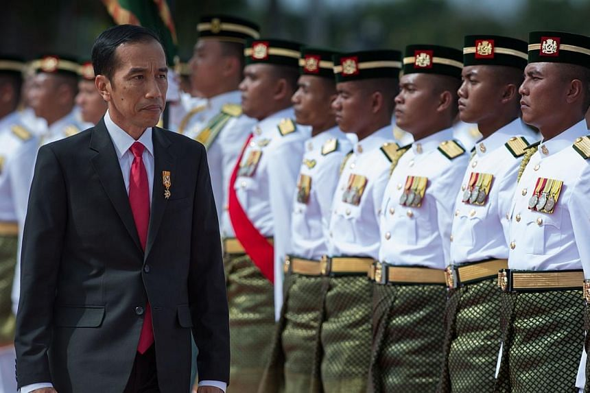 Indonesia's President Joko Widodo inspecting the Royal Malay Regiment Guard of Honour during a welcoming ceremony at the Bunga Raya complex at Kuala Lumpur International Airport in Sepang on Feb 5, 2015. -- PHOTO: AFP