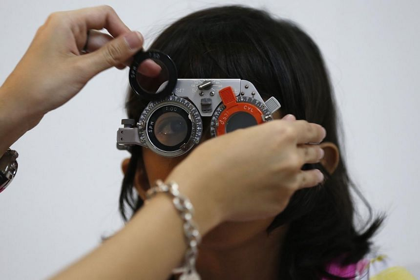 A girl getting her eyes checked for myopia. A China study said poor kids are far less likely to be nearsighted than their wealthier peers. -- PHOTO: ST FILE
