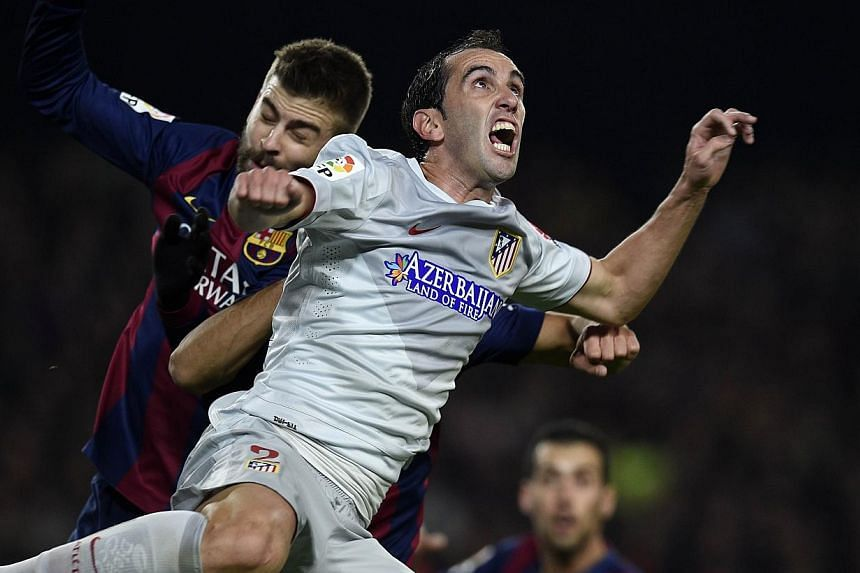 Atletico Madrid defender Diego Godin (right) vies with Barcelona'sGerard Piqueduring their Spanish league football match at the Camp Nou stadium in Barcelona on Jan 11, 2015. Godin has hit out at the media's labelling of his team's playin