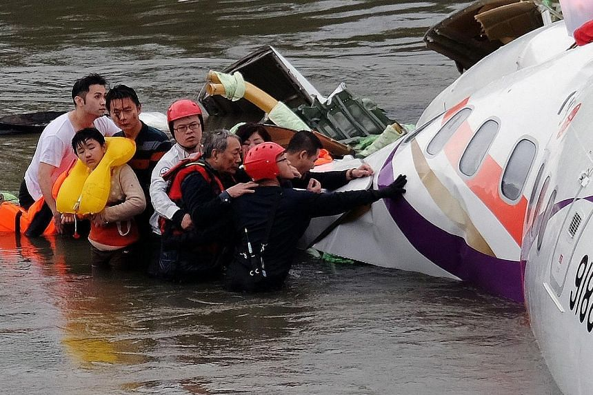 Rescue personnel (in helmets) help passengers as they wait to be transported to land from the wreckage of a TransAsia ATR 72-600 turboprop plane that crash-landed into the Keelung river outside Taiwan's capital Taipei in New Taipei City on Feb 4, 201