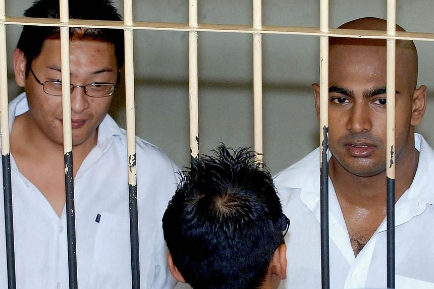 """In this file photograph taken on Feb 14, 2006, two Australian drug traffickers Andrew Chan (left) and Myuran Sukumaran (right), the ringleaders of the """"Bali Nine"""" drug ring, are seen in a holding cell while awaiting court trial in Denpasar, on Bali i"""