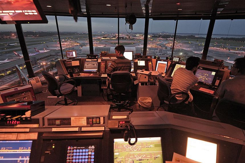 Air traffic controllers working inside the Changi Airport control tower. -- PHOTO: ST FILE