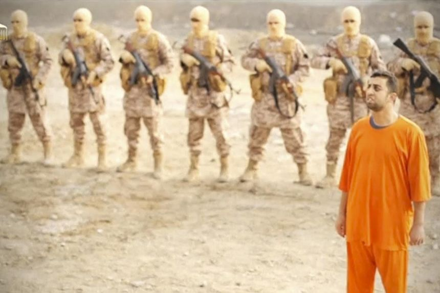Islamic State captive, Jordanian pilot Muath al-Kasaesbeh, stands in front of a row of armed militia in this photo still of a video released on social media. He was later seen being gruesomely burnt alive in a black cage. -- PHOTO: REUTERS