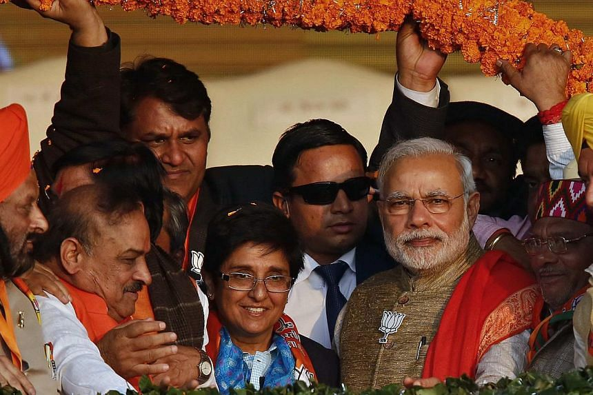 Supporters of India's ruling Bharatiya Janata Party (BJP) present a garland to Prime Minister Narendra Modi (front third right) during a campaign rally ahead of state assembly elections in New Delhi on Jan 31, 2015. He faces the first real test of hi