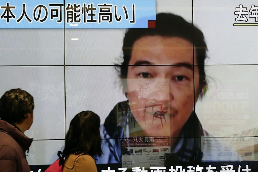 An image of journalist Kenji Goto with news reporting he had been killed by Islamic State in Iraq and Syria (ISIS) militants is seen in Tokyo on Feb 1,2015. A small elite crew of police runners equipped with cameras will take part in the Tokyo