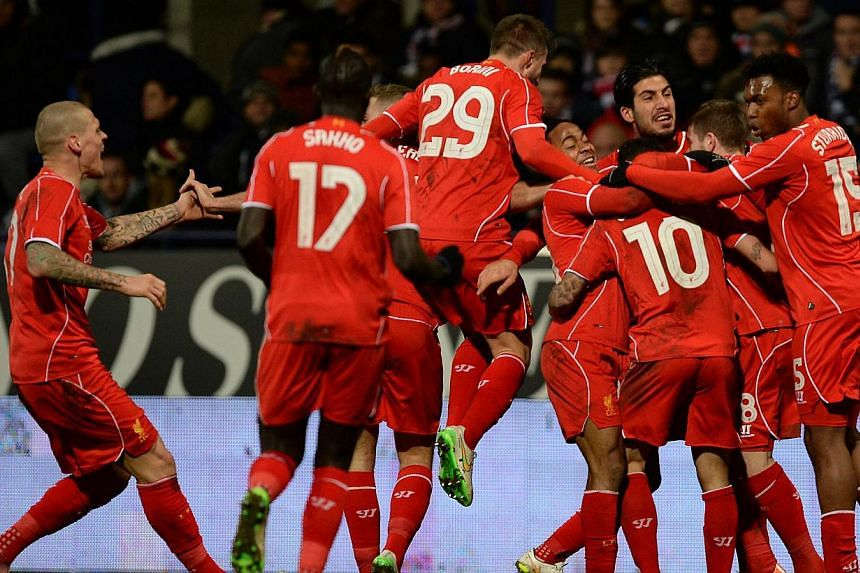 Liverpool's players celebrate after Phillipe Coutinho (10) scored the winning goal during the FA Cup fourth round replay match between Bolton Wanderers and Liverpool in Bolton, Britain on Feb 4, 2015. Premier League giants Liverpool on Thur