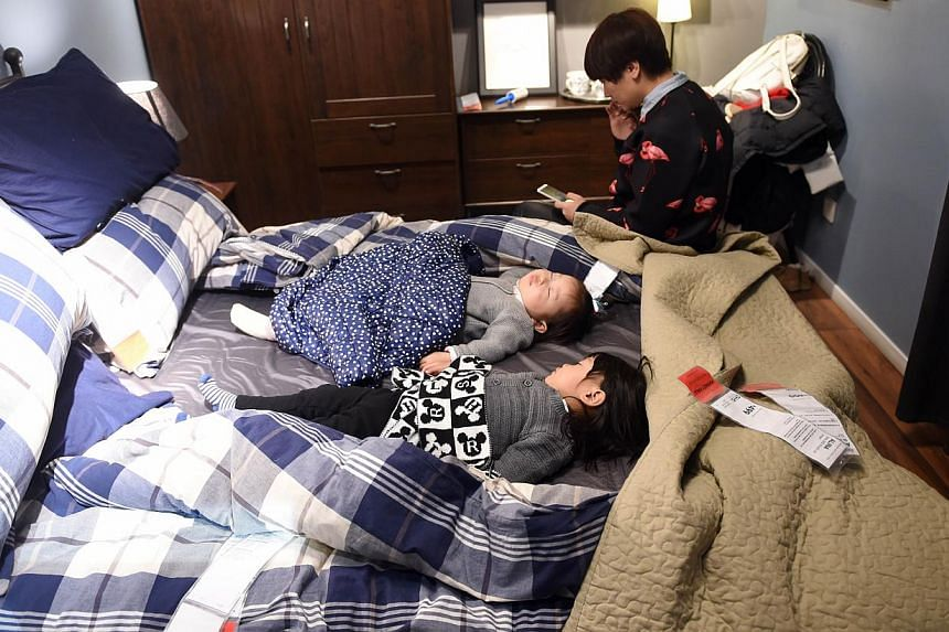 This picture taken on Jan 19, 2015, shows a Chinese woman sitting beside two sleeping babies on a display bed at a furniture store in Beijing.The National Sleep Foundation, an authority on official sleep guidelines in the United States, has rel