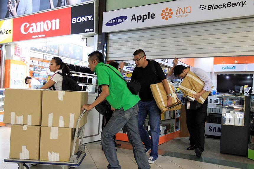 (Above) Business remains slow on the first and second floors of Sim Lim Square. (Below) Police on Nov 16 removing documents and products from Mobile Air shop, whose shady sales tactics drew complaints.