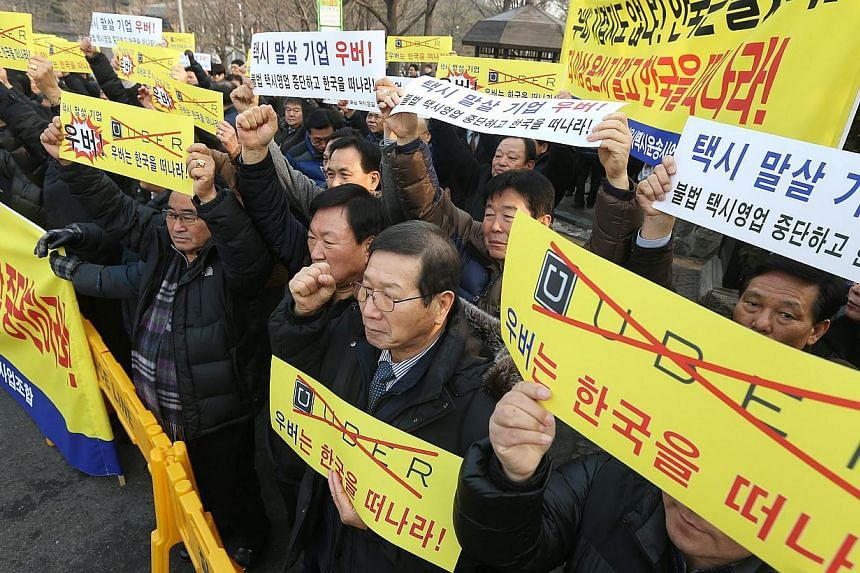 South Korean taxi drivers and taxi industry officials hold a rally in downtown Seoul, South Korea, on Feb 4, 2015, demanding that web-based taxi company Uber withdraw from the South Korean market. -- PHOTO: EPA