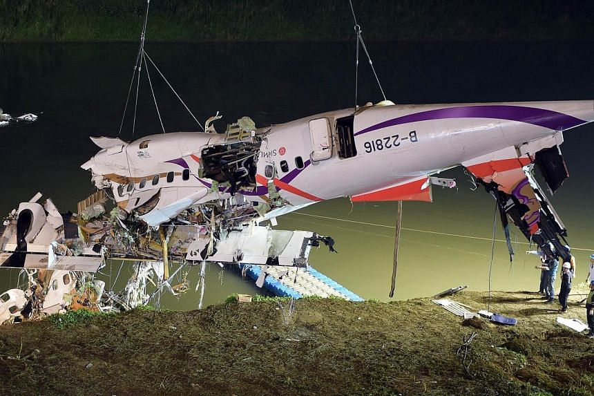 Rescuers lift the wreckage of the TransAsia ATR 72-600 out of the Keelung river at New Taipei City on Feb 4, 2015. -- PHOTO: AFP