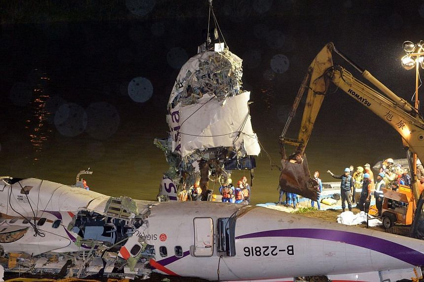 The front section of the wreckage of the TransAsia ATR 72-600 turboprop plane is lifted onto the Keelung river bank outside Taiwan's capital Taipei in New Taipei City on Feb 5, 2015. -- PHOTO: AFP