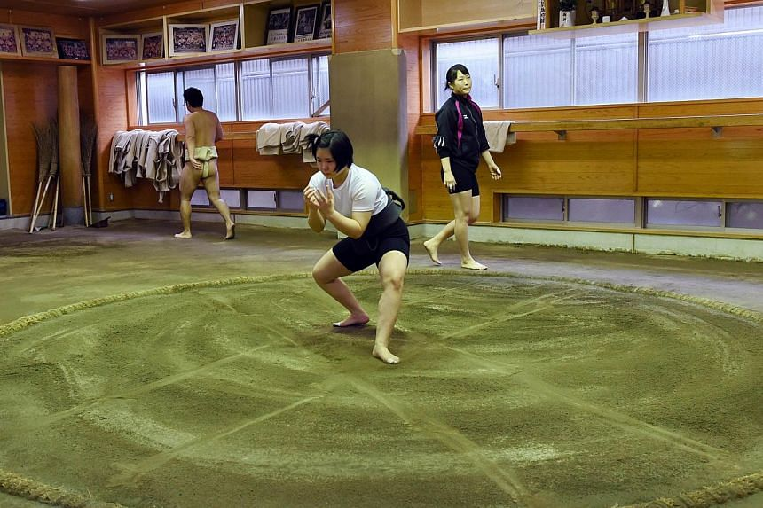 Female sumo wrestlers Sayaka Matsuo (centre) and Shiori Kanehira (back right) attending a training session at Nihon University's sumo club in Tokyo. -- PHOTO: AFP