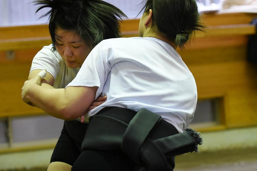 Female sumo wrestler Sayaka Matsuo (left) fighting with her teammate Shiori Kanehira during a training session at Nihon University's sumo club in Tokyo. -- PHOTO: AFP
