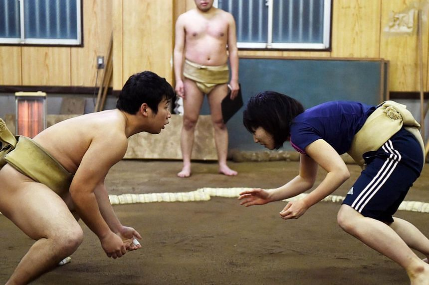Female sumo wrestler Anna Fujita (right) fighting with her teammate during a training session at Tokyo University's sumo club in Tokyo. -- PHOTO: AFP