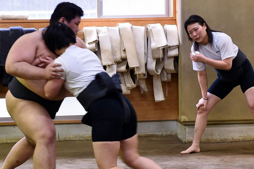 Female sumo wrestlers Shiori Kanehira (right) and Sayaka Matsuo (centre) attending a training session at Nihon University's sumo club in Tokyo. -- PHOTO: AFP