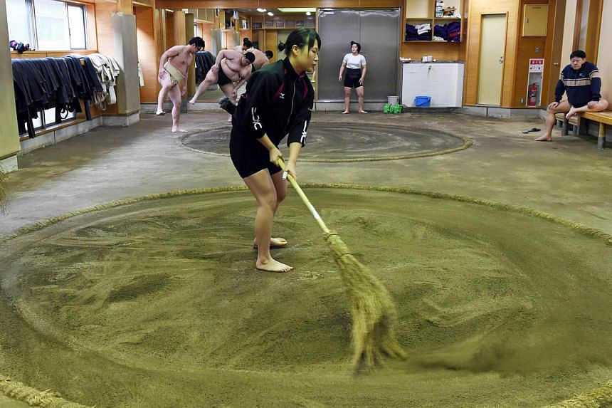 Female sumo wrestler Shiori Kanehira cleaning the ring during a training session at Nihon University's sumo club in Tokyo. -- PHOTO: AFP