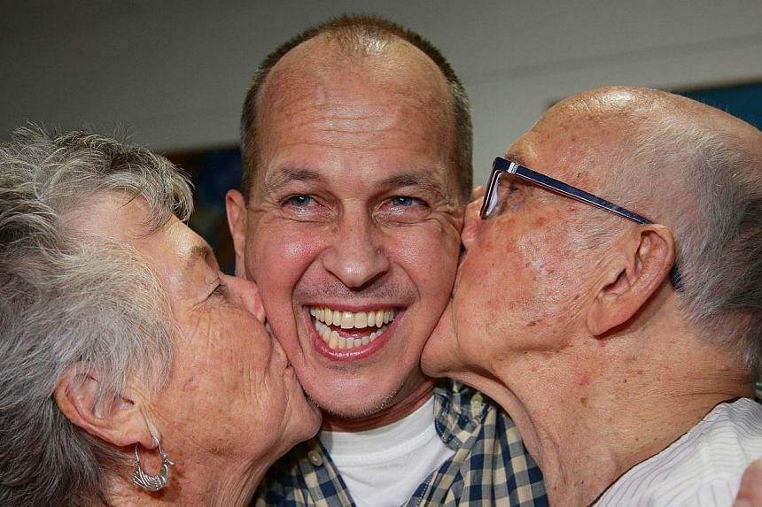 Al-Jazeera journalist Peter Greste is kissed by his mother Lois (left) and father Juris upon his arrival at Brisbane's international airport in the early hours of Feb 5, 2015. -- PHOTO: AFP