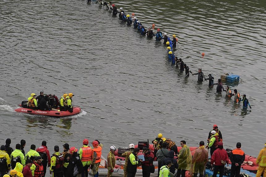 Rescuers and divers search for missing passengers at the crash site of the Transasia ATR 72-600 turboprop plane in the Keelung river in New Taipei City on Feb 6, 2015. The blackbox data and voice recorders of a TransAsia plane that crashed into